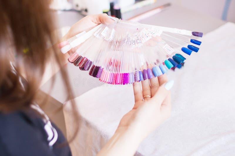 Manos de la mujer joven que eligen color del clavo Manos y muestras manicured femeninas del color del clavo imagen de archivo libre de regalías