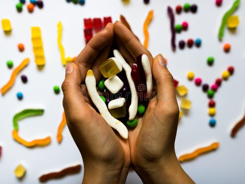 Manos de la mujer llenas de caramelos con el fondo colorido foto de archivo
