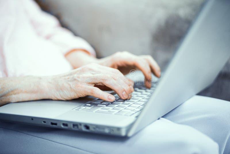 Manos de la mujer madura que mecanografían en el ordenador portátil foto de archivo