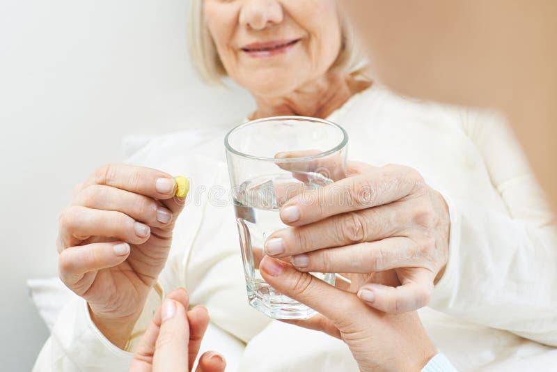 Manos de la mujer mayor con el vidrio de agua foto de archivo libre de regalías