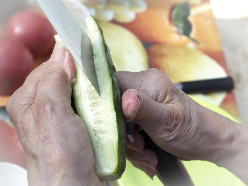 Manos de la mujer mayor que preparan las verduras frescas para la comida campestre foto de archivo