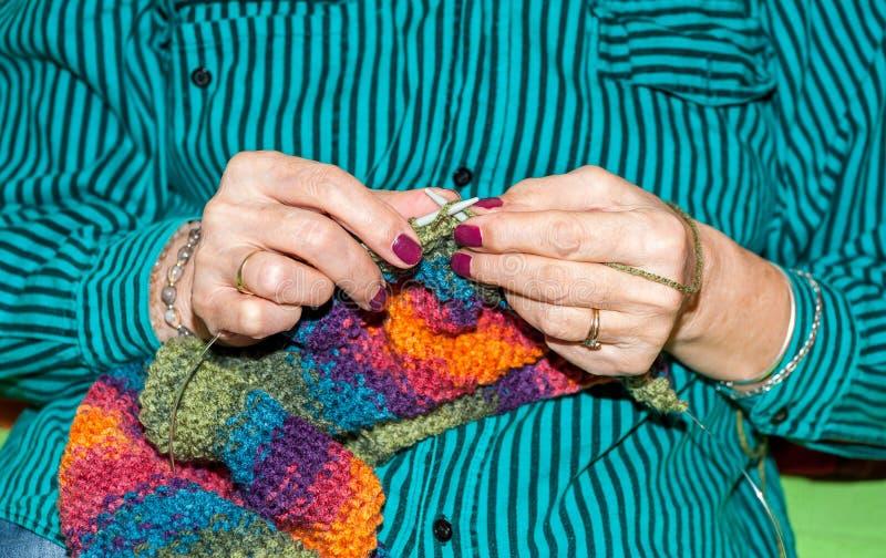 Manos de la mujer mayor que sostienen agujas que hacen punto y las lanas coloreadas multi para el woolwork del suéter caliente po fotos de archivo