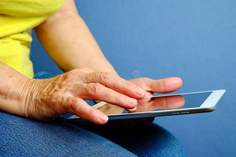 Manos de la mujer mayor que sostienen la tableta fotografía de archivo libre de regalías
