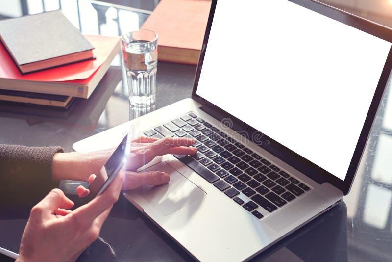 Manos de la mujer de la opinión del primer usando smartphone y el ordenador portátil móviles Espacio para la disposición de diseñ imágenes de archivo libres de regalías