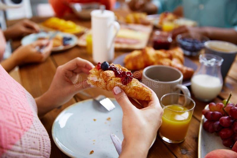 Manos de la mujer que comen el cruasán para el desayuno foto de archivo libre de regalías