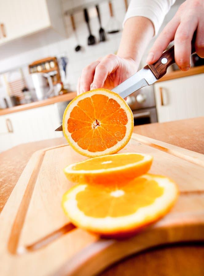 Manos de la mujer que cortan la naranja foto de archivo