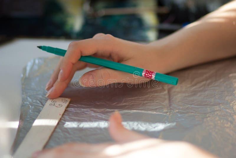 manos de la mujer que dibujan la línea en el papel con el rotulador y la regla imagen de archivo libre de regalías