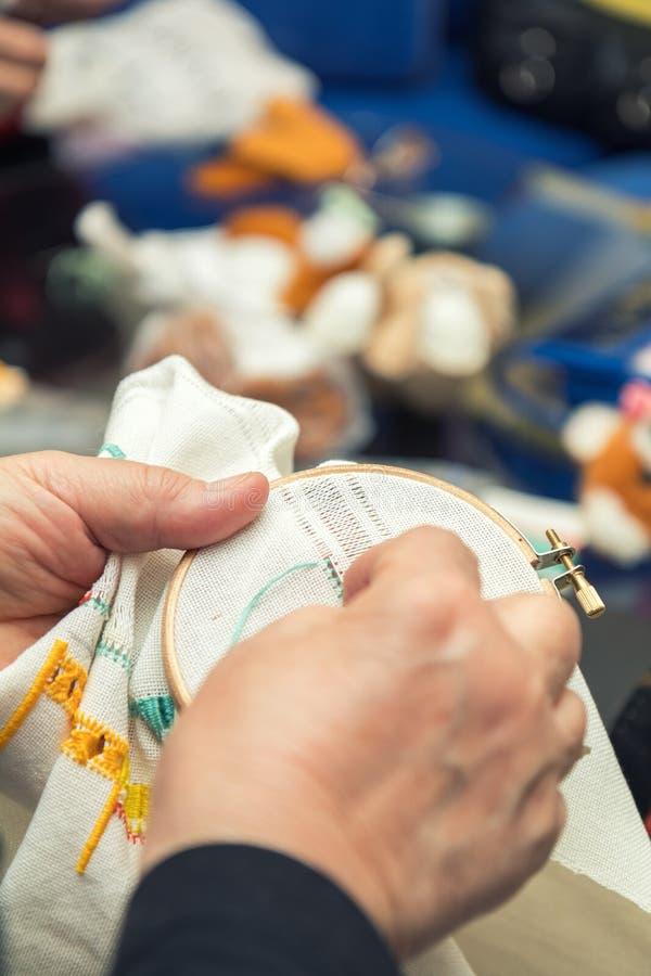 Manos de la mujer que hacen el bordado a cielo abierto imagen de archivo libre de regalías
