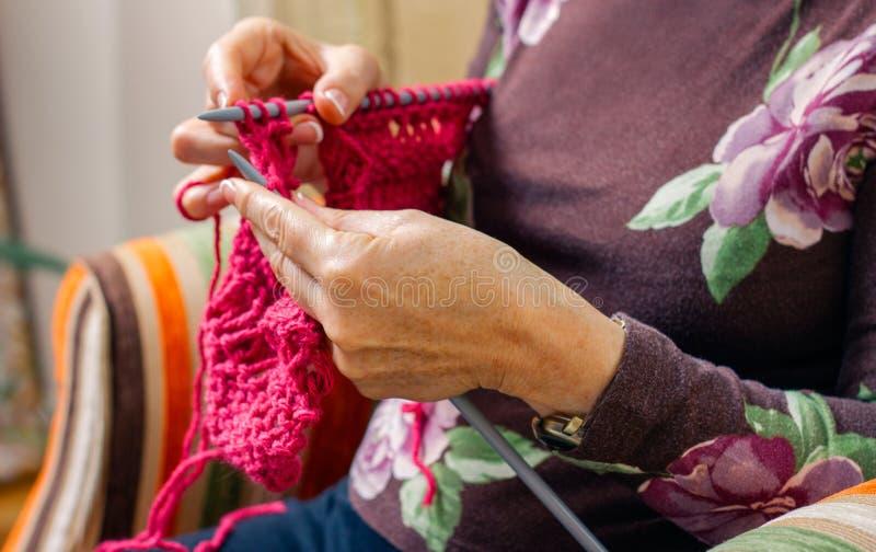 Manos de la mujer que hacen punto un suéter de las lanas imagen de archivo