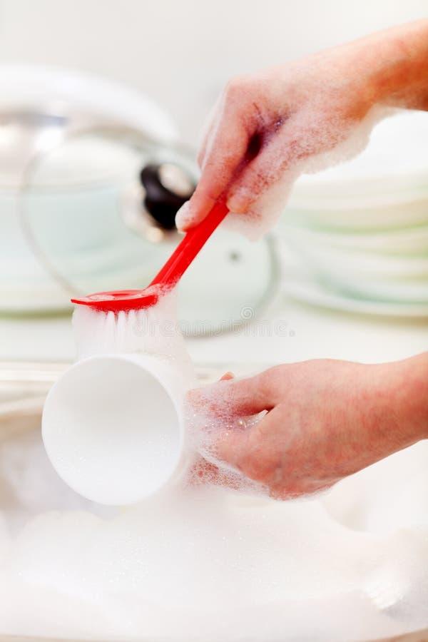 Manos de la mujer que lavan platos fotografía de archivo libre de regalías