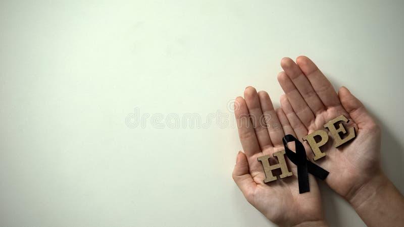 Manos de la mujer que muestran la cinta negra a la c?mara, conciencia del melanoma, c?ncer de piel fotografía de archivo libre de regalías