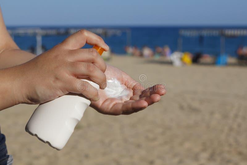 Manos de la mujer que ponen la protección solar en la playa fotografía de archivo