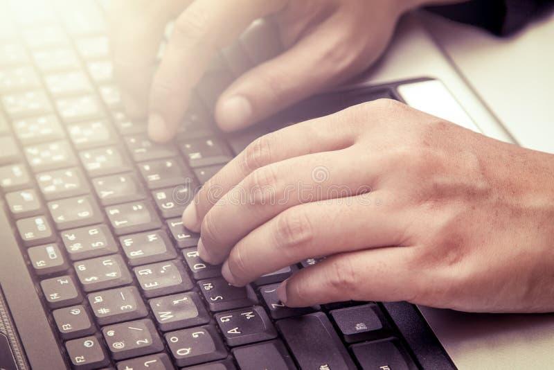 Manos de la mujer que pulsan en el teclado de la computadora portátil imágenes de archivo libres de regalías