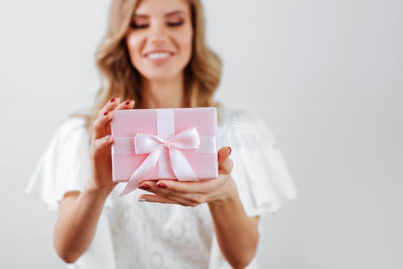 Manos de la mujer que sostienen la caja de regalo rosada foto de archivo libre de regalías