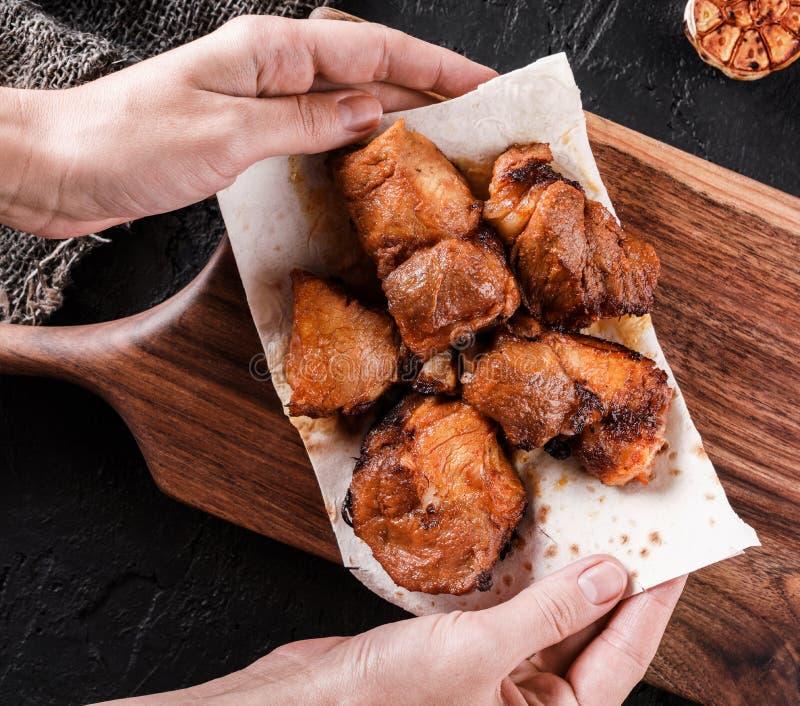 Manos de la mujer que sostienen la carne o el kebab asada a la parrilla, shashlik en el pan Pita en el tablero de madera Visi?n s fotos de archivo