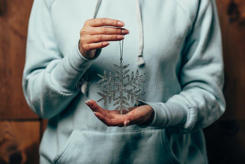 Manos de la mujer que sostienen el juguete del copo de nieve imágenes de archivo libres de regalías