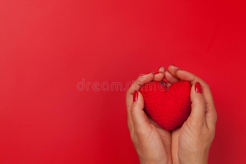 Manos de la mujer que sostienen el juguete rojo del corazón foto de archivo