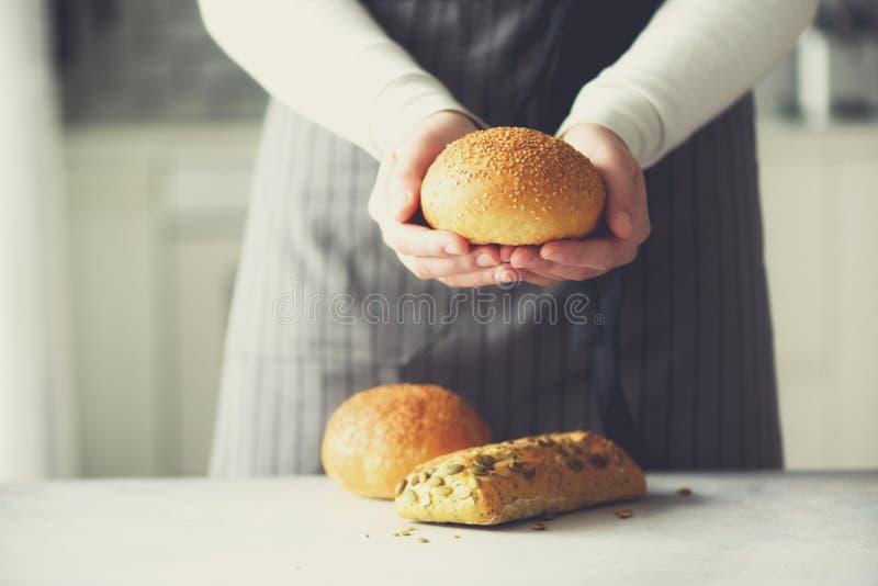 Manos de la mujer que sostienen el pan recientemente cocido Bollo, galleta, concepto de la panadería, comida hecha en casa, consu imagen de archivo