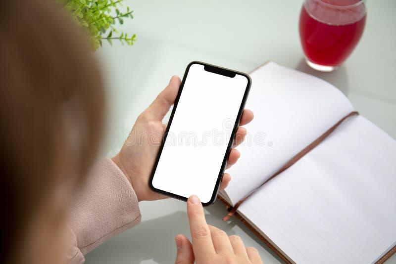 Manos de la mujer que sostienen el teléfono del tacto con la pantalla aislada sobre la tabla en la oficina fotografía de archivo libre de regalías