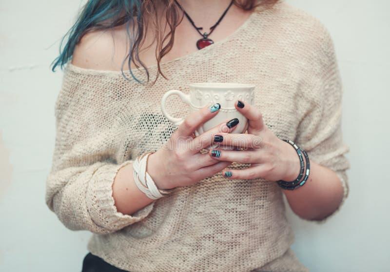Manos de la mujer que sostienen la taza de café imagen de archivo