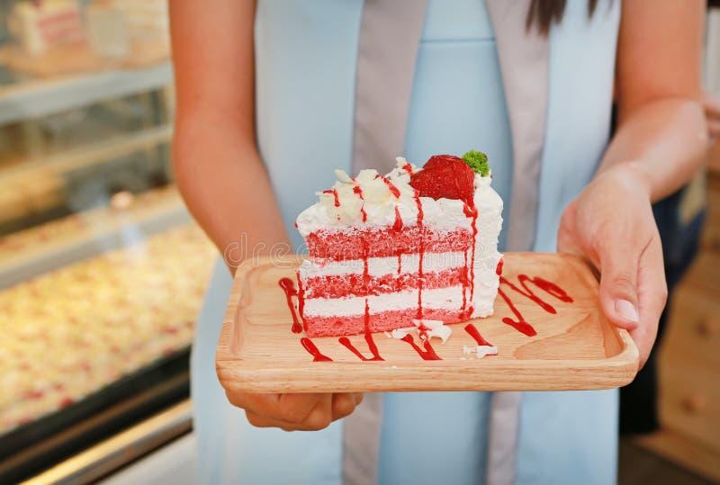 Manos de la mujer que sostienen las tortas de la fresa en el café imagen de archivo
