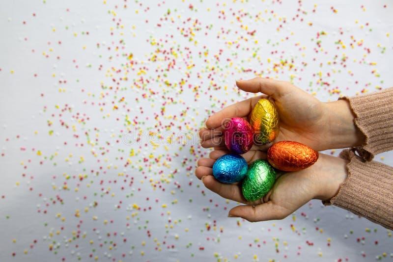 Manos de la mujer que sostienen los huevos de Pascua coloridos del chocolate con el fondo blanco y confeti borroso colorido foto de archivo libre de regalías