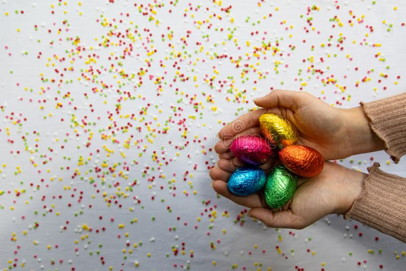Manos de la mujer que sostienen los huevos de Pascua coloridos del chocolate con el fondo blanco y confeti borroso colorido fotografía de archivo libre de regalías