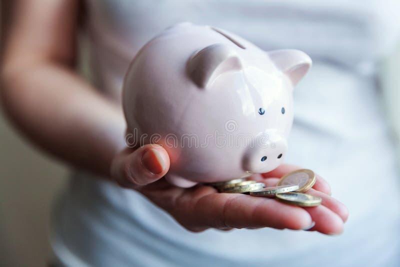 Manos de la mujer que sostienen monedas rosadas de la hucha y del euro fotografía de archivo libre de regalías