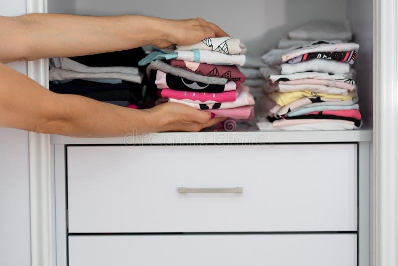 Manos de la mujer que sostienen la ropa de lino colorida de las materias textiles de la pila imagenes de archivo