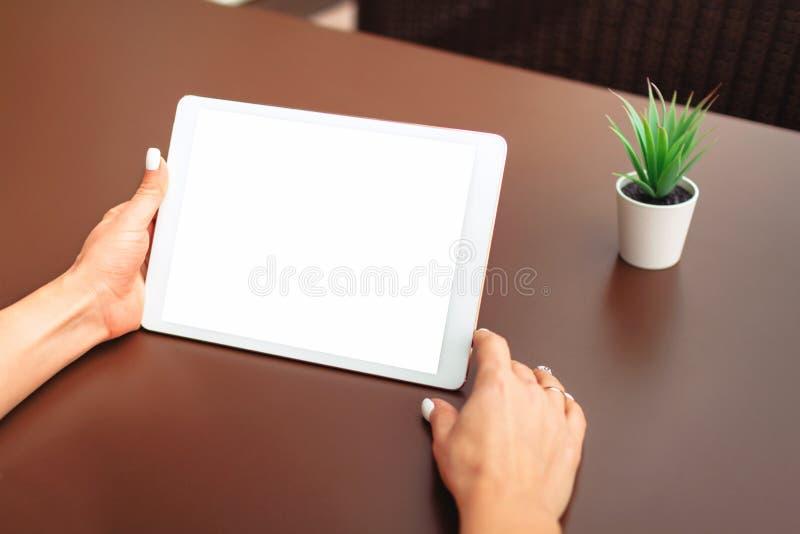 Manos de la mujer que sostienen la tableta con la pantalla blanca foto de archivo