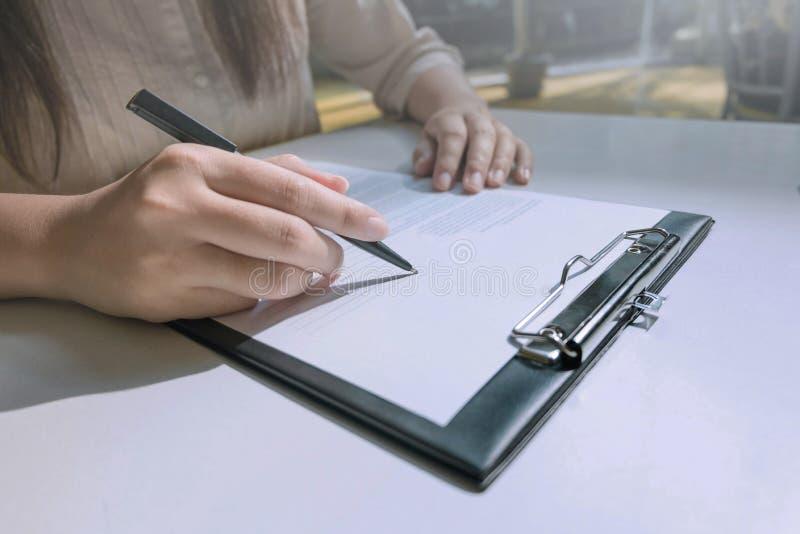 Manos de la mujer que terminan el formulario de inscripción foto de archivo