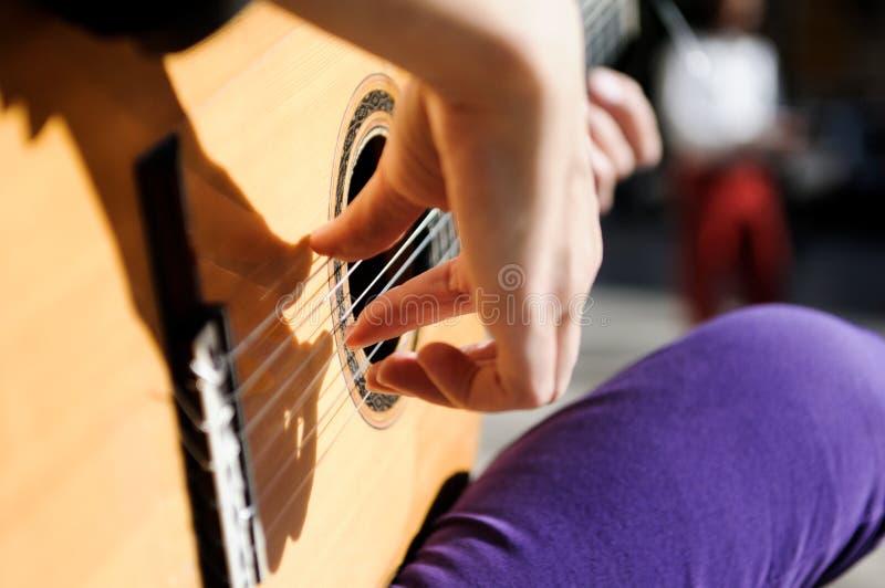 Manos de la mujer que tocan la guitarra española imagenes de archivo