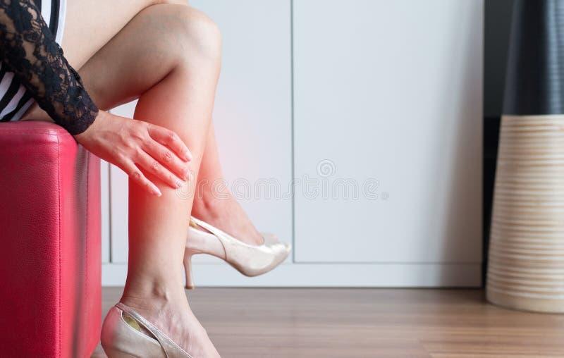 Manos de la mujer que tocan su músculo del becerro porque sufre del dolor del imflammation de los pies, cierre para arriba imagenes de archivo