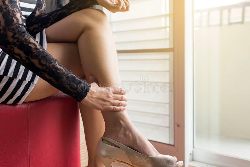Manos de la mujer que tocan su músculo del becerro porque sufre del dolor del imflammation de los pies, cierre para arriba fotos de archivo libres de regalías