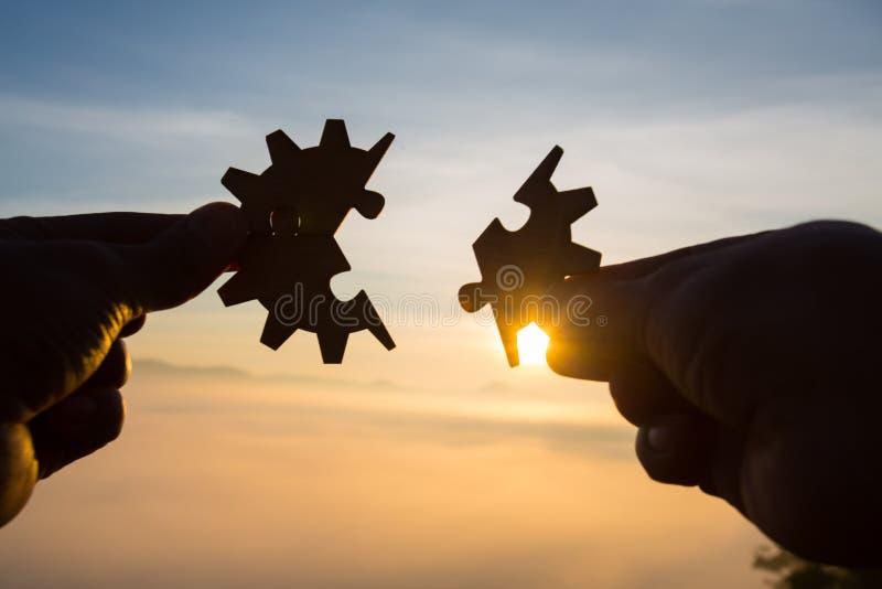 Manos de la mujer de la silueta que conectan el pedazo del rompecabezas de los pares contra la salida del sol, las soluciones del fotos de archivo libres de regalías