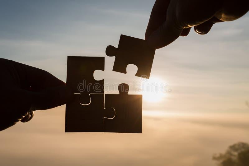 Manos de la mujer de la silueta que conectan el pedazo del rompecabezas de los pares contra su imagenes de archivo