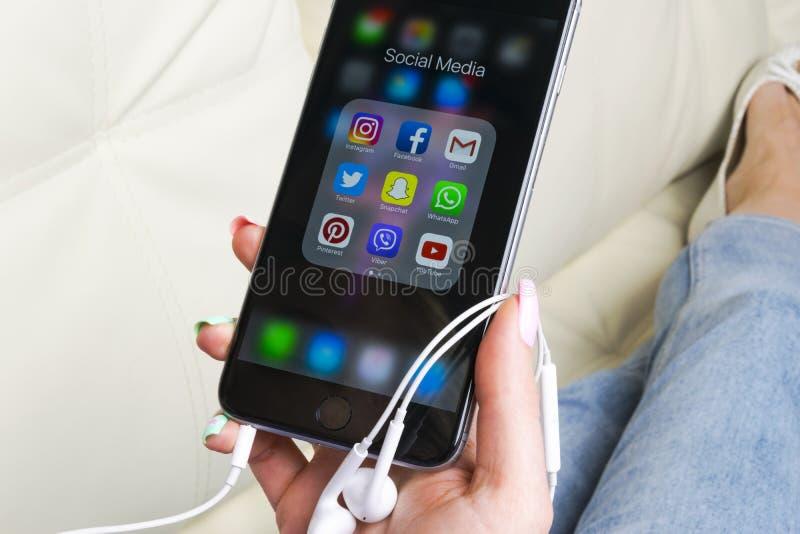 Manos de la mujer usando el iphone 7 con los iconos del medios facebook social, instagram, gorjeo, uso de Google en la pantalla C fotografía de archivo libre de regalías