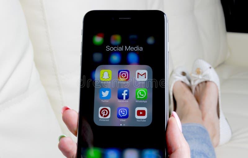 Manos de la mujer usando el iphone 7 con los iconos del medios facebook social, instagram, gorjeo, uso de Google en la pantalla C fotos de archivo libres de regalías