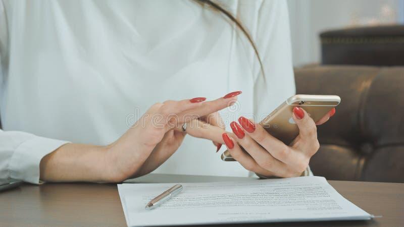 Manos de la mujer usando el teléfono celular en restaurante imagen de archivo