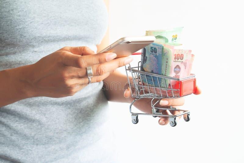 Manos de la mujer usando el teléfono móvil y el carro de la compra el sostenerse con Th imagen de archivo