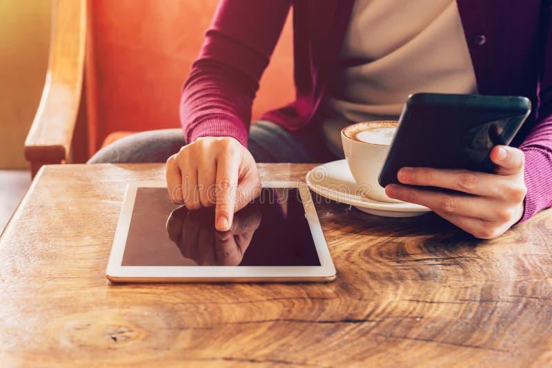 Manos de la mujer usando la tableta del ordenador y el smartphone el sostenerse fotos de archivo libres de regalías