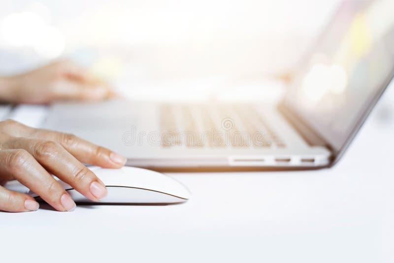 Manos de la mujer usando ratón con el teclado del ordenador portátil imagen de archivo libre de regalías