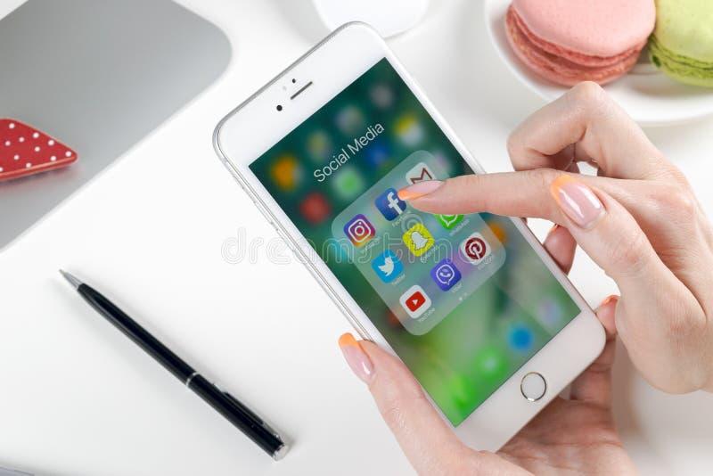 Manos de la mujer usando smartphone con los iconos del medios facebook social, instagram, gorjeo, uso de Google en la pantalla Sm imagenes de archivo
