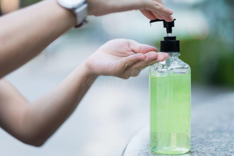 Manos de la mujer utilizando un dispensador de gel para desinfectantes, contra el coronavirus Novel o la enfermedad del virus Cor fotografía de archivo