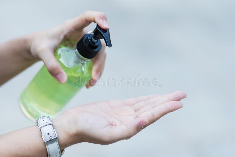Manos de la mujer utilizando un dispensador de gel para desinfectantes, contra el coronavirus Novel o la enfermedad del virus Cor fotografía de archivo libre de regalías