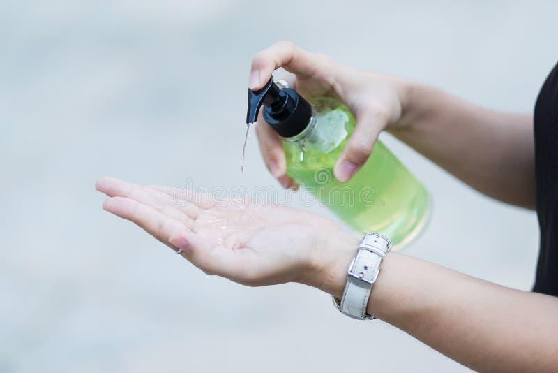 Manos de la mujer utilizando un dispensador de gel para desinfectantes, contra el coronavirus Novel o la enfermedad del virus Cor fotos de archivo libres de regalías