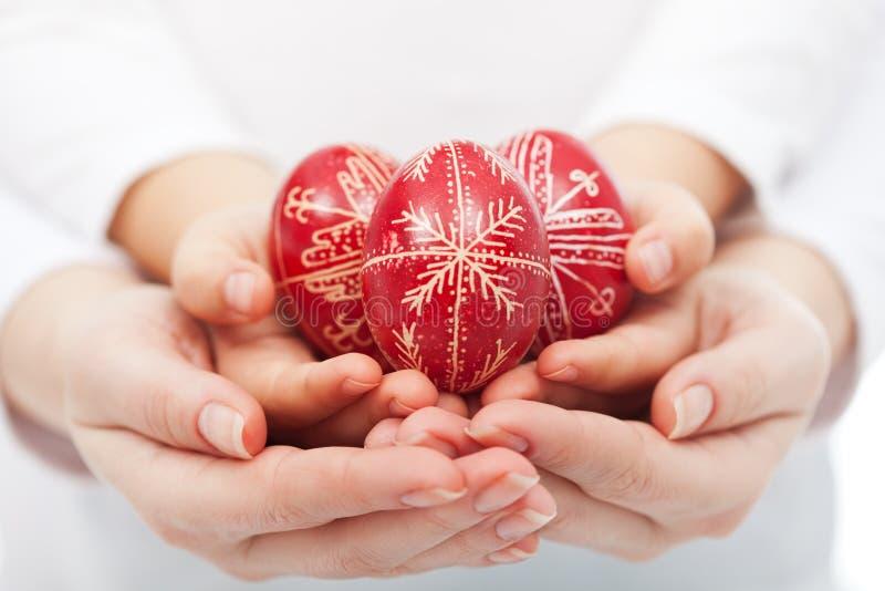 Manos de la mujer y del niño que sostienen los huevos de Pascua foto de archivo