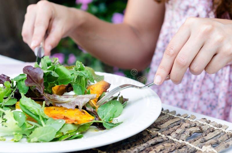 Manos de la mujer y ensalada verde durante una comida fotografía de archivo