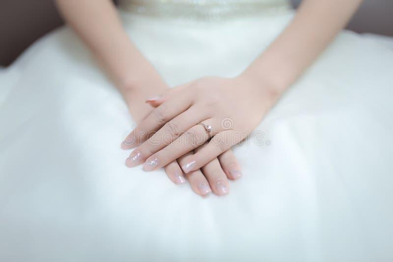 Manos de la novia blando y suavemente endecha en su revestimiento fotografía de archivo libre de regalías