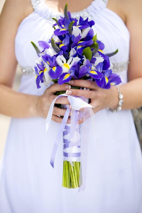 Manos de la novia que sostienen el ramo de la boda de flores violetas y blancas fotos de archivo